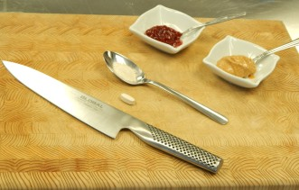 Spoon, knife, jam, peanut butter, and pill on chopping board