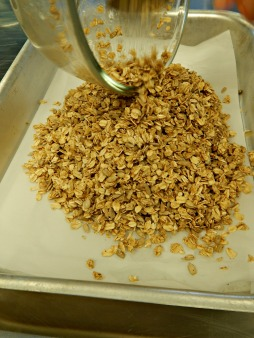 spread granola ingredients into a lined baking pan