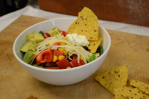 Bowl of taco salad with tortilla chips on chopping board