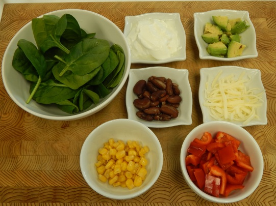 Toppings of spinach, yogurt, avocado, corn, red peppers, cheese, beans in separated bowls