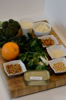 Broccoli, kale, almonds, sardines, tofu, couscous in bowls on chopping board