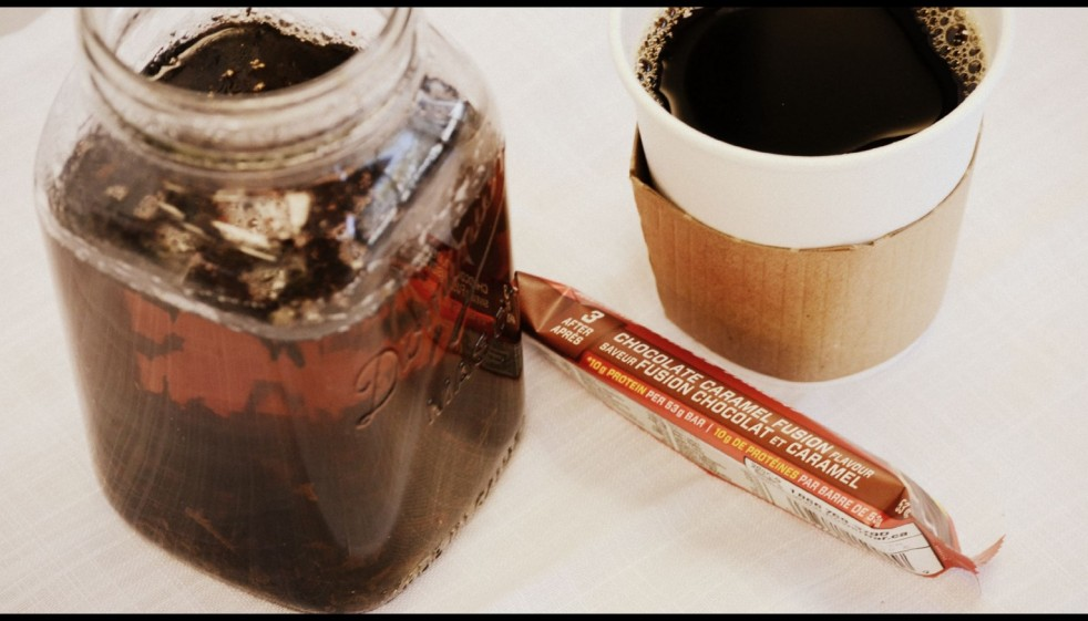 Tea in mason jar, energy bar, cup of coffee