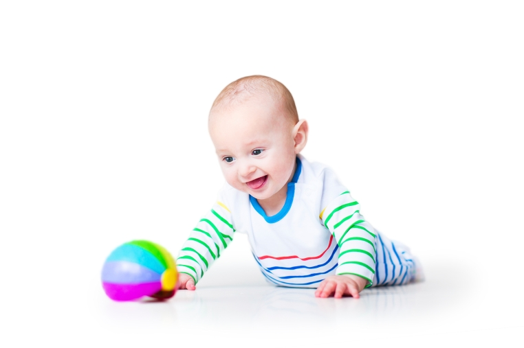 Happy laughing baby on tummy playing with colourful ball