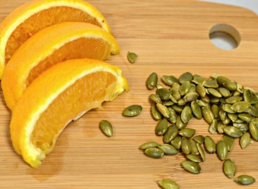 orange slices and pumpkin seeds on chopping board