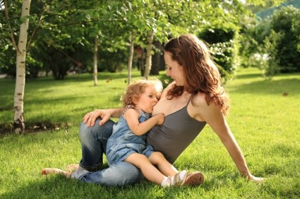 Older child breastfeeding in park