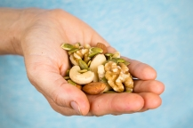 Hand holding a variety of nuts and seeds
