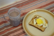 Cup filled with strawberry smoothie, plate with toast & egg