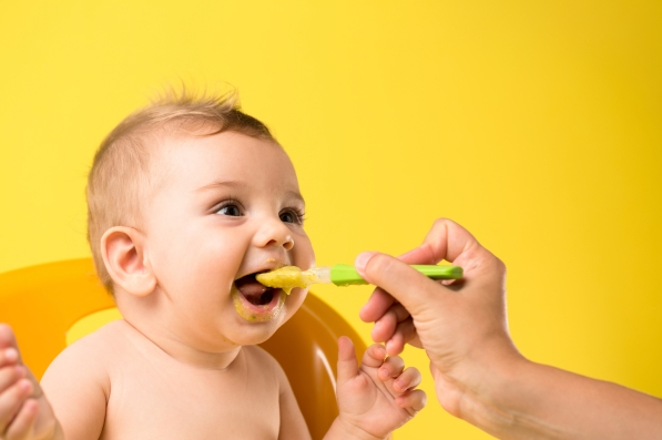 Baby being fed by spoon in front of a vivid yellow background.