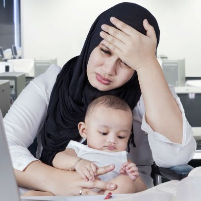 Woman holding baby looking stressed