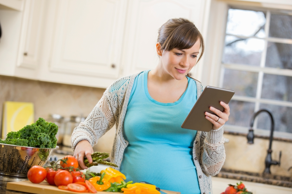 Pregnant adult in kitchen with fresh vegetables