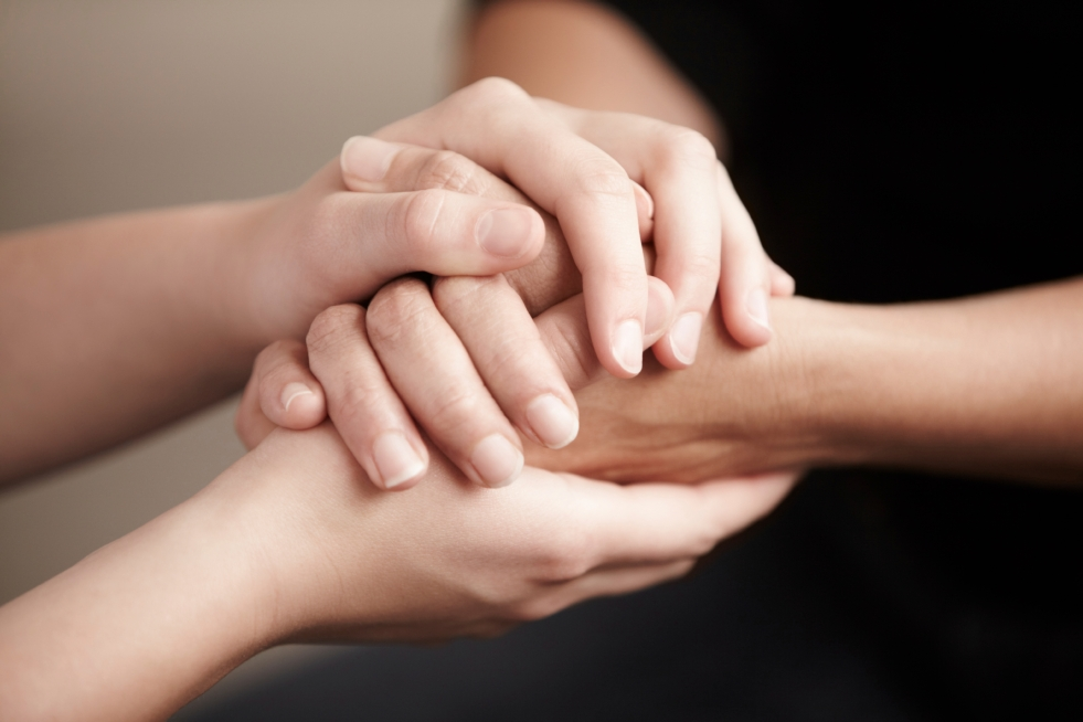 Two people's hands being held tightly together