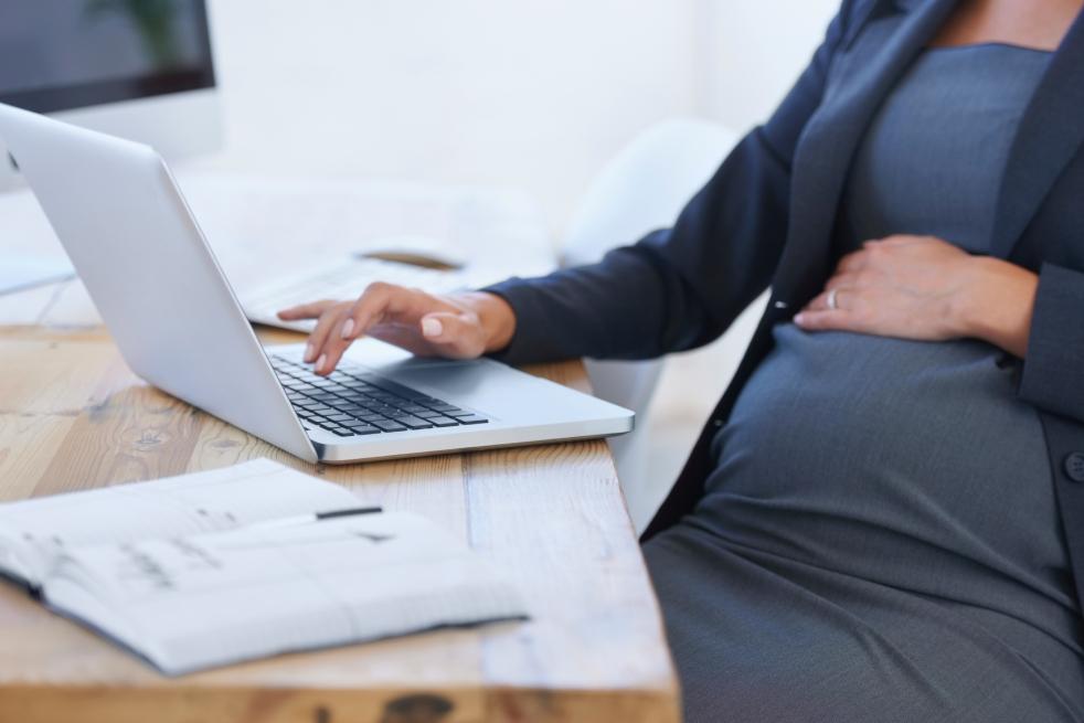 Expectant parent using laptop on desk
