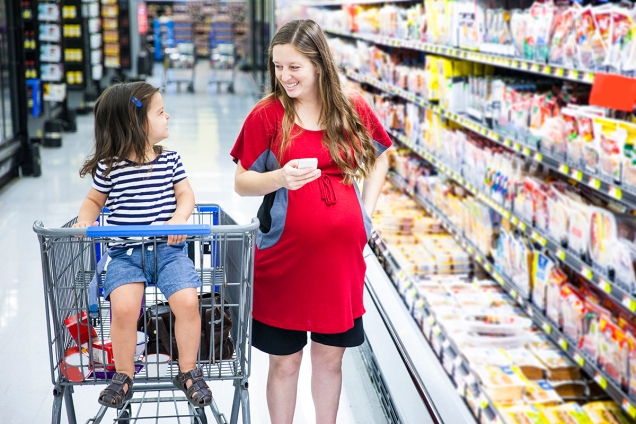 Pregnant woman doing her grocery shopping with her daughter sitting in a shopping cart
