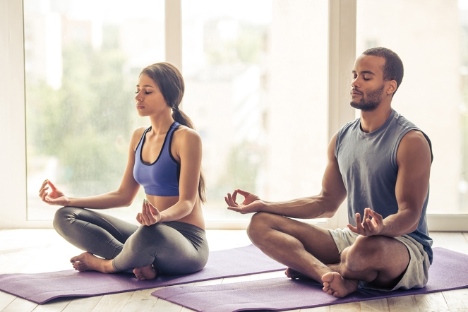 Afro American couple in sports clothes is meditating sitting in lotus position on mat while doing yoga at home