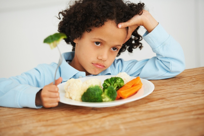 little boy looking upset and sitting in front of a plate of vegetables