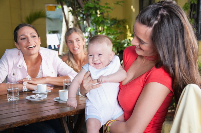 Three Smiling woman on outdoor patio where one is holding a baby