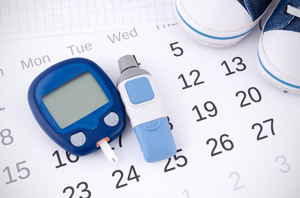 Blue glucose monitor with testing strip on top of calendar.