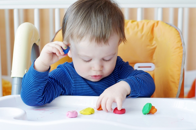Toddler sitting in highchair playing with playdough