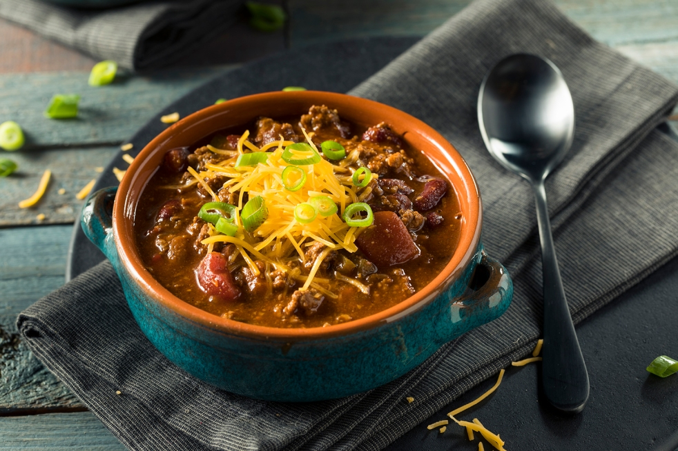 Bowl of Homemade Beef Chili Con Carne with Cheese and Onions