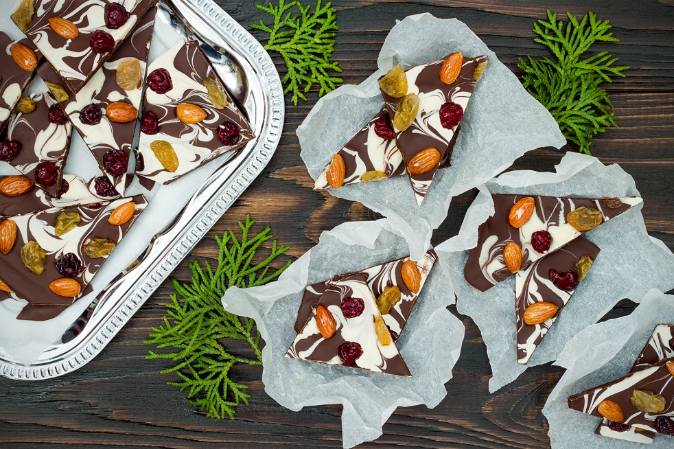 Holiday chocolate bark with dried fruits and nuts on a dark wood background.