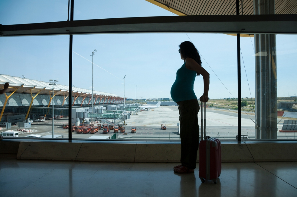 pregnant silhouette of an individual waiting to fly in airport hall