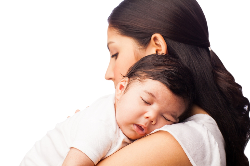Hispanic parent holding baby sleeping on parent's shoulder