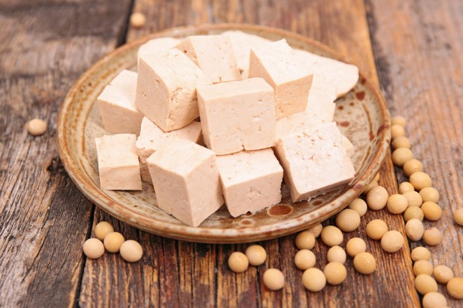 Cubed tofu on a brown platter with soy beans on wooden table