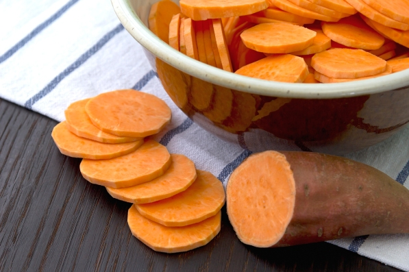 Raw sweet potato on a vintage wooden table, in a bowl on top of a towel