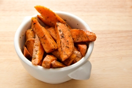 a bowl of baked herbed sweet potato wedges on a wooden surface