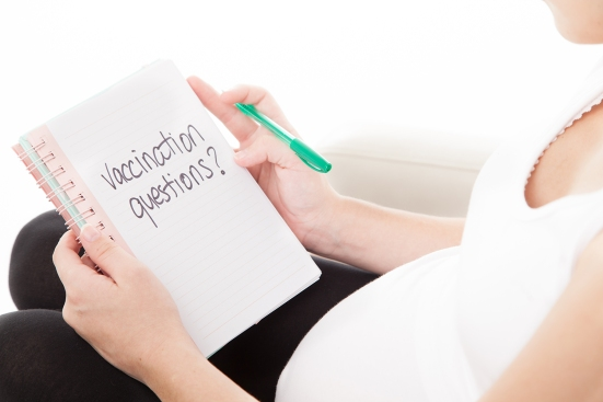 "Expectant parent preparing to write in a ""Vaccination Questions?"" notebook"