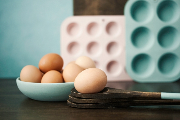 Pastel colored kitchen equipment with eggs in a bowl and one on brown wooden spoon