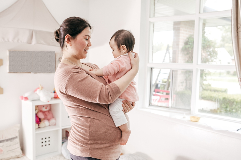 Pregnant individual holding baby