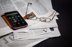 mobile device and glasses on top of newspapers