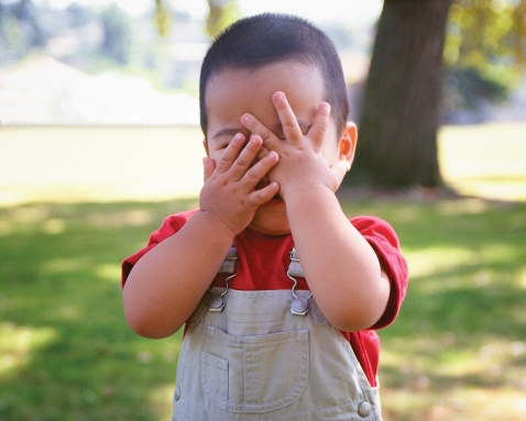 Toddler covering face with hands