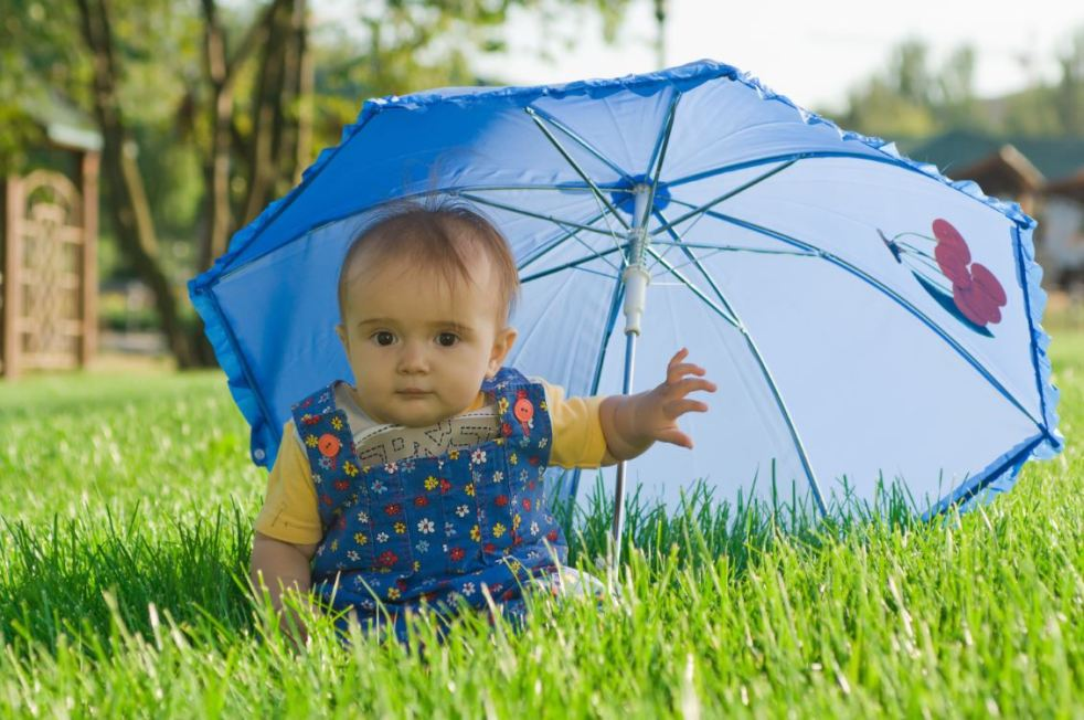 Baby sitting up under a blue umbrella for shade