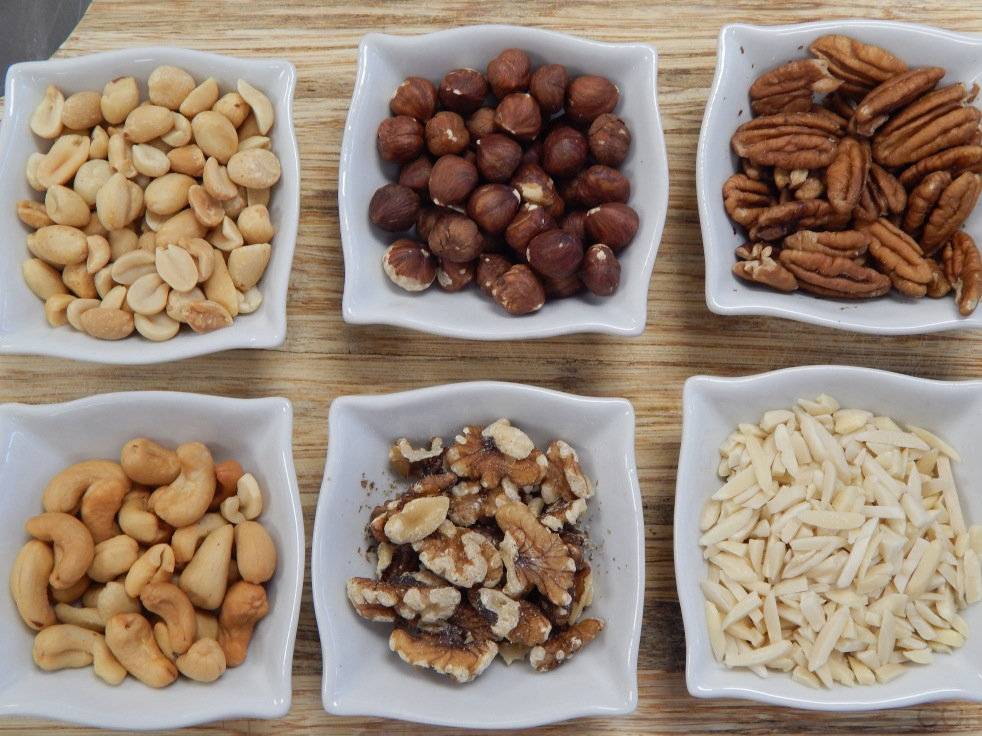Variety of nuts separated in white square bowls