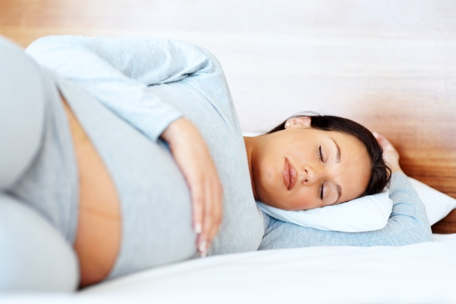 Pregnant individual sleeping on their side in bed