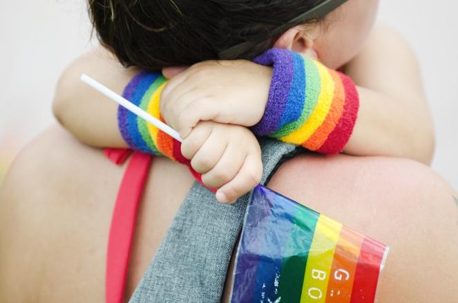 Child hugging parent at Pride celebration