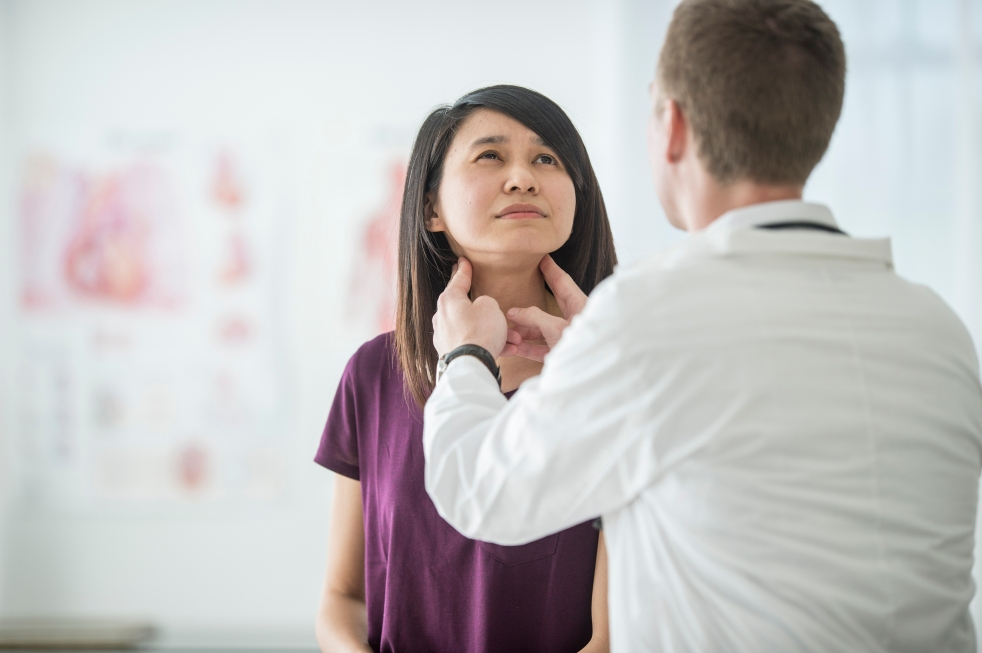 Individual in Doctor's office having a thyroid examination