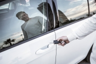 Individual facing a white car, locking door with key in hand.