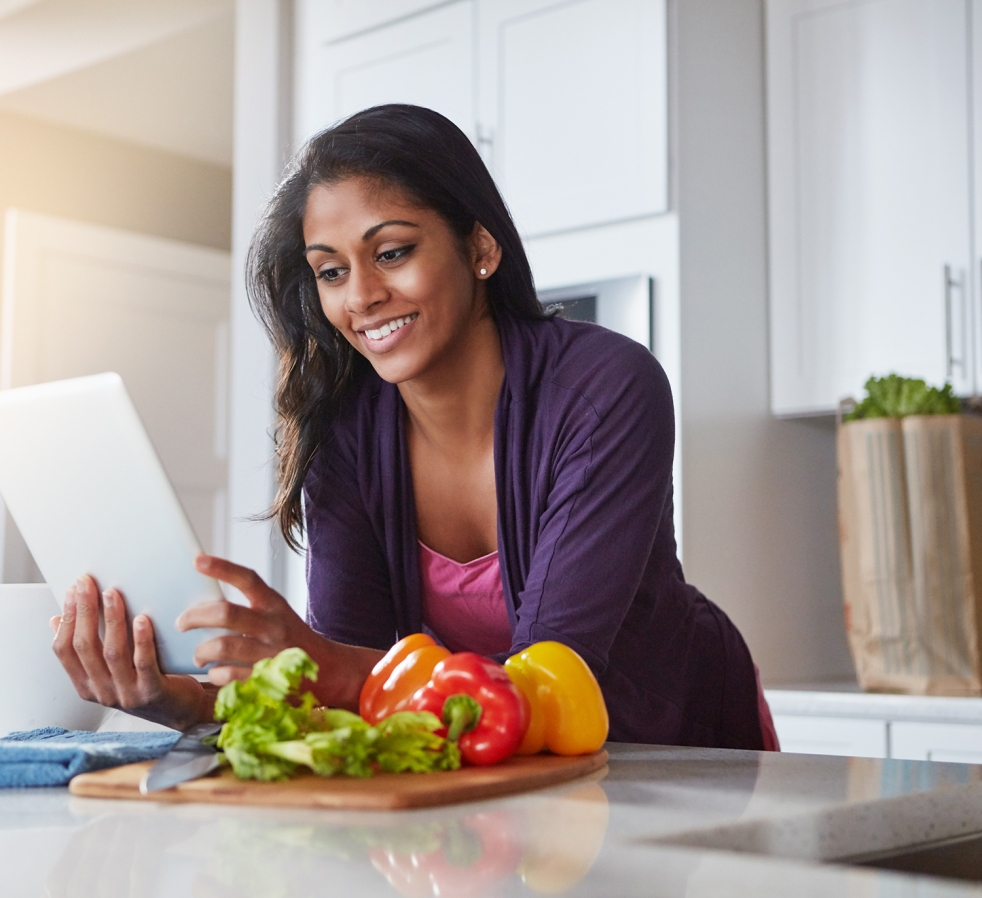 young woman using a digital tablet while preparing a healthy meal at home