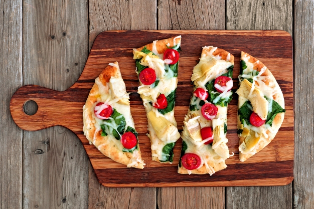 Healthy flat bread pizza with melted mozzarella, tomatoes, spinach and artichokes, above view on wooden paddle board