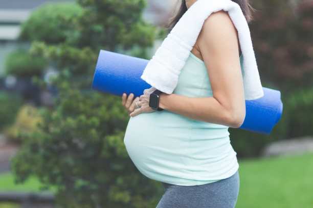 Pregnant individual outside holding a blue yoga mat with a white towel on shoulder