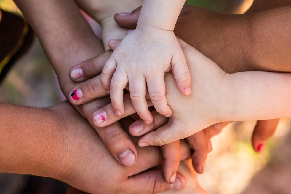 A group of adult and child hands piled together