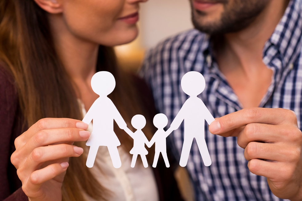 couple holding paper chain of a family.