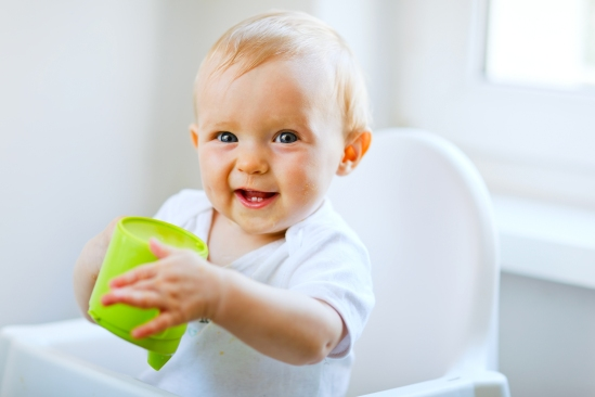 Cheerful baby sitting in chair and holding a green cup