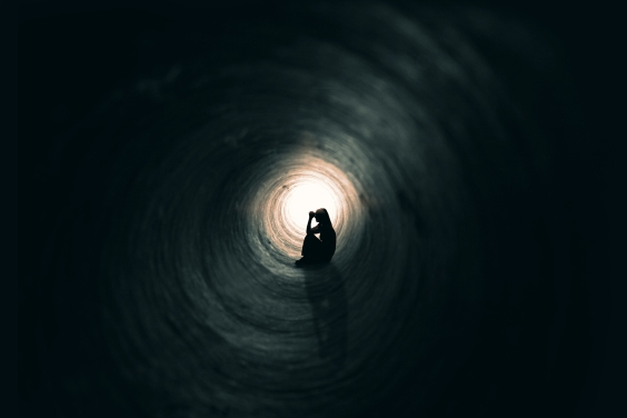 silhouette of a person sitting in a dark tunnel with a light at the end.