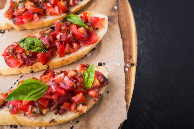 bruschetta with tomatoes and basil on wood board