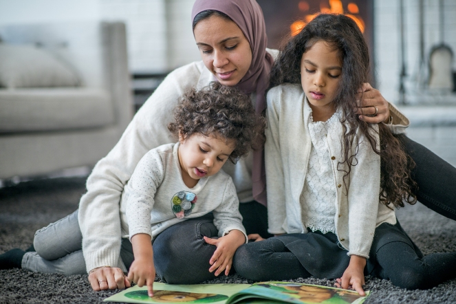 Mother and two children sitting on the carpet and reading a book together.