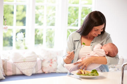 Parent With Baby Eating Healthy Meal In Kitchen